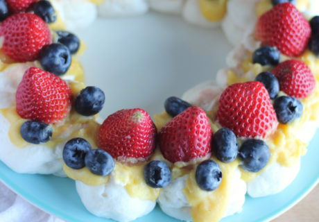 A low carb Pavlova with Lemon Curd and fresh strawberries and blueberries on top of it. It is on a blue place.