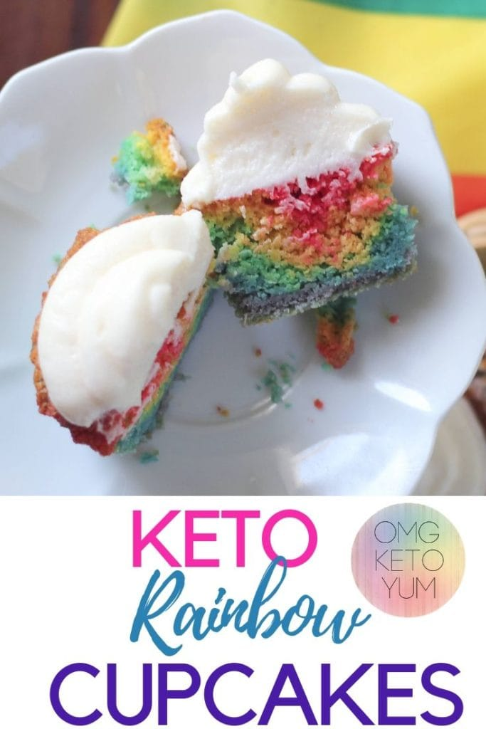 A rainbow Cupcake sliced in half to show the rainbow layers inside. These cupcakes are topped with a dairy free, sugar free keto frosting.
